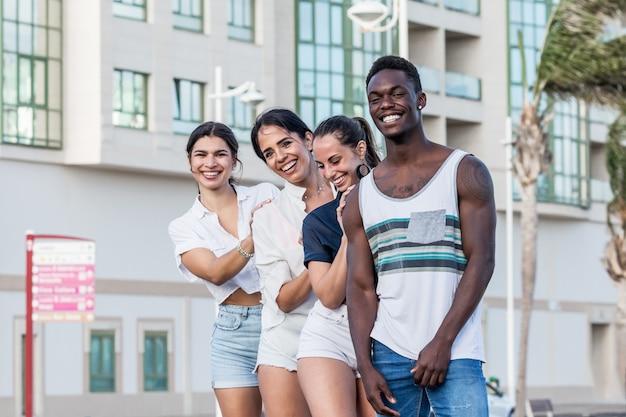 Grupo de amigos multiétnicos posando na cidade