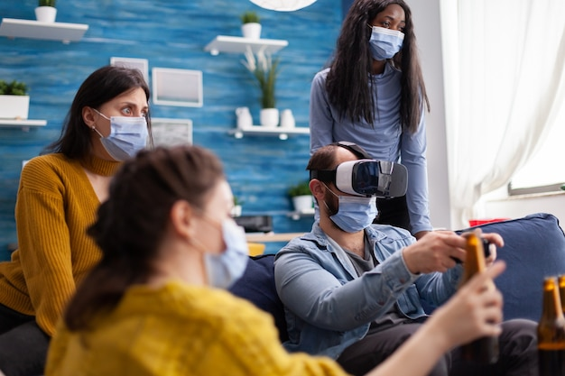 Grupo de amigos multiétnicos se divertindo jogando videogame usando fone de ouvido de realidade virtual e joystick usando máscara facial mantendo o distanciamento social. diversas pessoas desfrutando de uma nova festa normal.