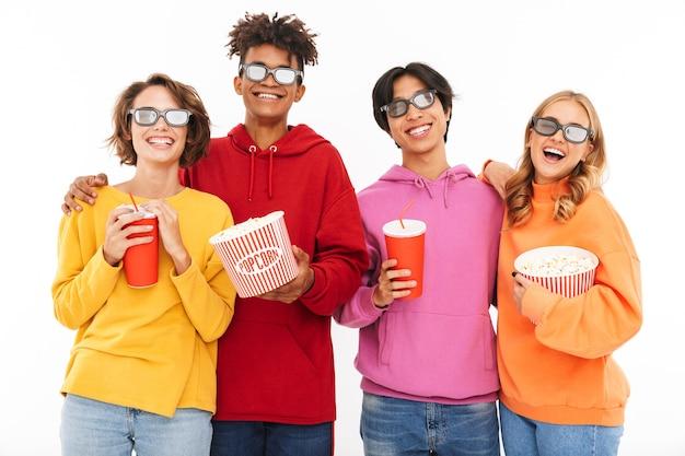 Grupo de amigos multirraciais alegres assistindo a um filme, comendo pipoca, bebendo refrigerante isolado