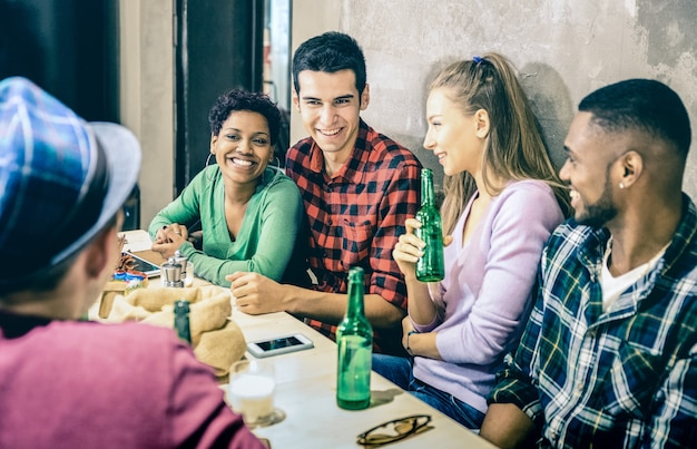 Grupo de amigos multirraciais bebendo cerveja e se divertindo em um restaurante fashion bar de coquetéis