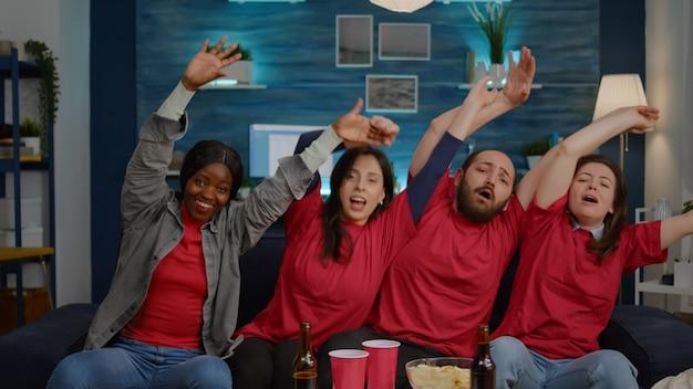 Grupo de amigos multirraciais curtindo assistir esportes na televisão