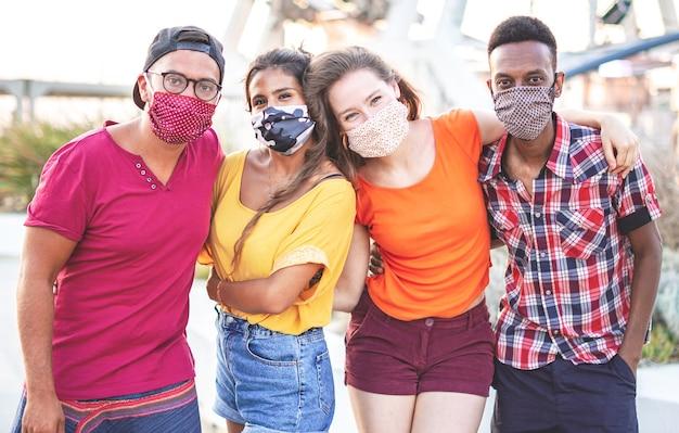 Grupo de amigos multirraciais tirando foto com máscara facial - jovens se divertindo nas férias - novo conceito de estilo de vida