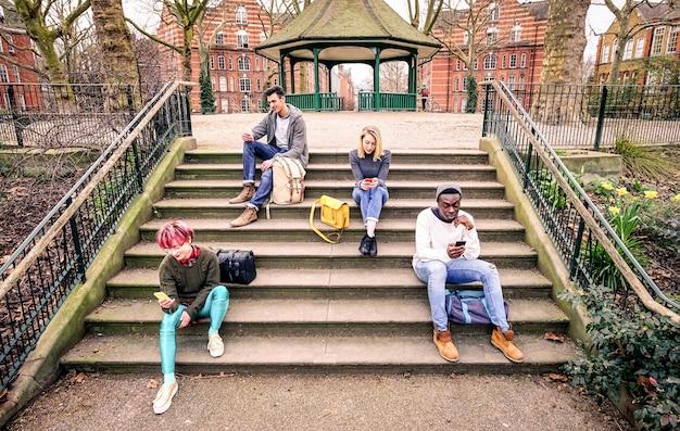 Grupo de amigos multirraciais usando telefone celular inteligente sentado na escada do parque