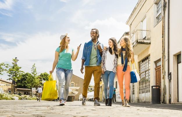 Grupo de amigos multirracial se divertindo juntos andando na rua da cidade