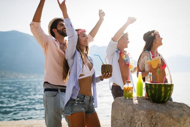 Grupo de amigos na praia, bebendo e se divertindo. festa de verão.