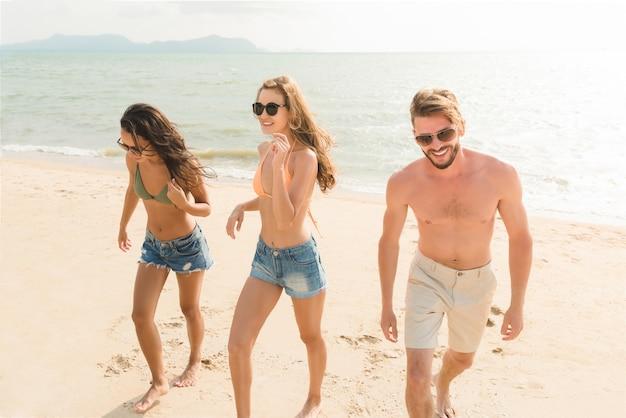 Grupo de amigos na praia de verão tropical bonita nos feriados