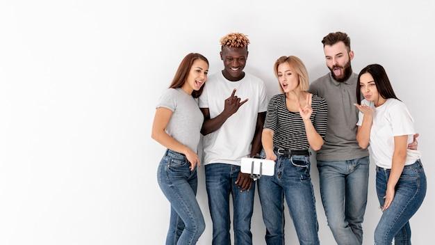 Grupo de amigos no espaço da cópia tirando selfies