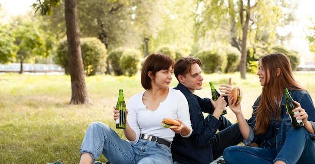 Grupo de amigos no parque com hambúrgueres e cerveja