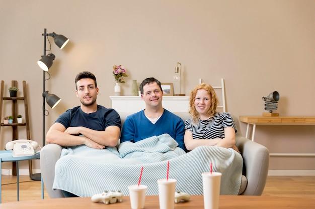 Grupo de amigos no sofá com copos de refrigerante e cobertor