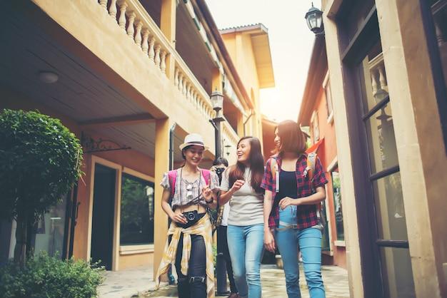 Grupo de amigos novos felizes que têm o divertimento andar na rua urbana. conceito de viagens de amizade.