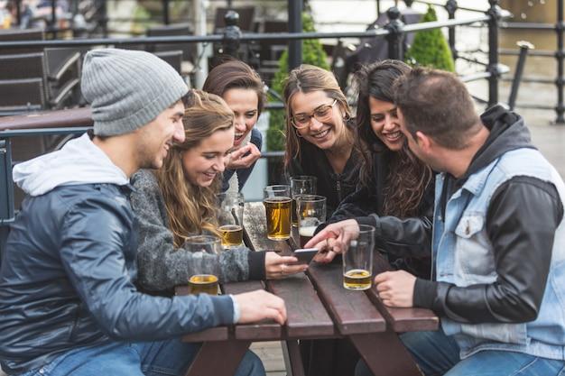 Grupo de amigos, olhando para o telefone inteligente no pub
