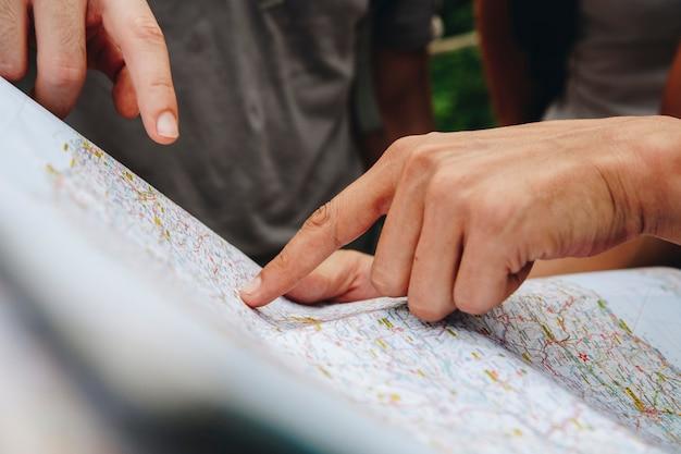 Grupo de amigos, olhando para um mapa juntos, viajar e conceito de trabalho em equipe