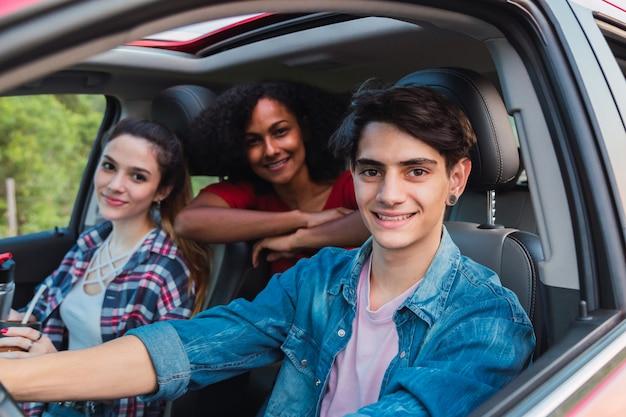 Grupo de amigos olhando pela janela de um carro em viagem