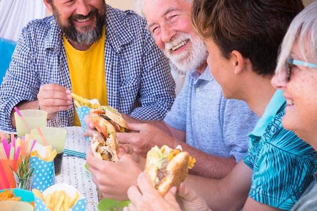 Grupo de amigos ou família almoçando juntos com hambúrguer e batatas fritas juntos - pessoas felizes celebrando juntos - com lixo e comida não saudável - gerações mistas