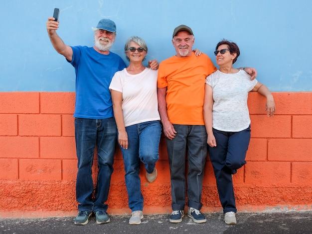 Grupo de amigos ou família em pé contra uma parede colorida - quatro idosos - conceito de ativo com aposentados