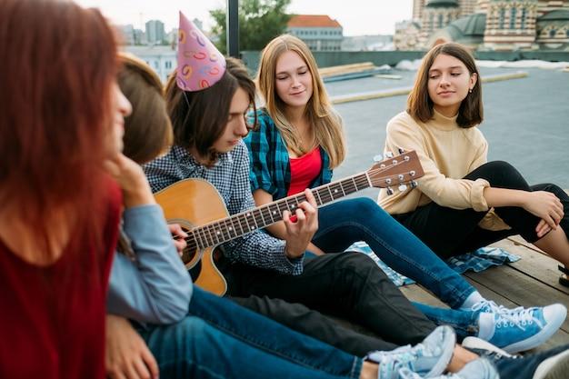 Grupo de amigos ouve músico tocando guitarra em uma festa no telhado. estilo de vida artístico do músico. lazer adolescentes