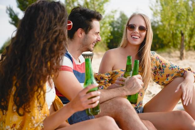 Grupo de amigos passando um bom tempo com garrafas de cerveja