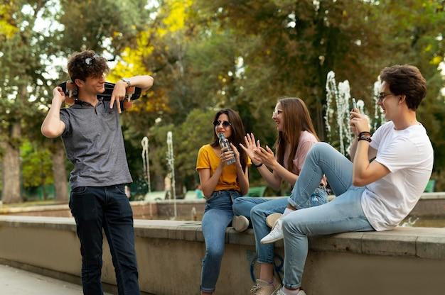 Grupo de amigos passando um tempo juntos ao ar livre perto da fonte Foto gratuita