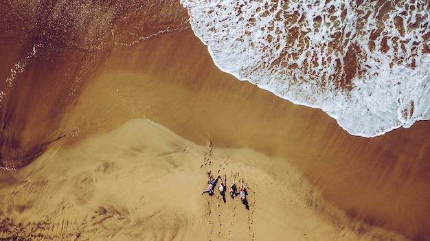 Grupo de amigos pessoas curtindo a praia deitada na areia vista aérea de cima com ondas connig verão férias viagens estilo de vida para homens e mulheres jovens durante o feriado paisagem colorida vertical