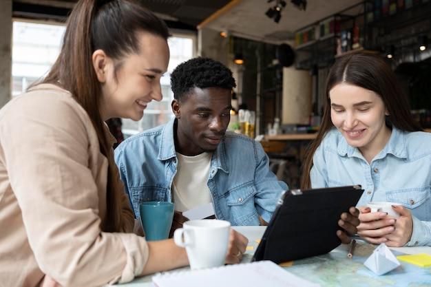 Grupo de amigos planejando uma viagem em um café