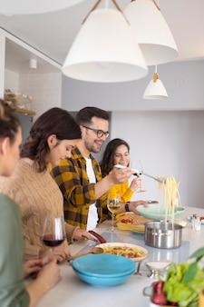 Grupo de amigos preparando a refeição na cozinha