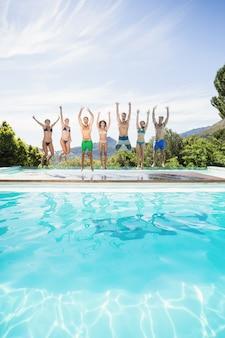 Grupo de amigos pulando na beira da piscina