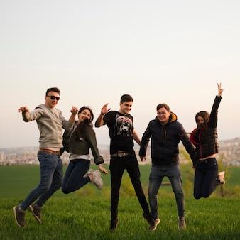 Grupo de amigos pulando na natureza