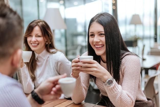 Grupo de amigos que comem o café junto em um restaurante.