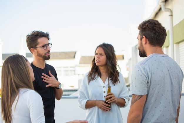 Grupo de amigos que compartilham notícias sobre uma garrafa de cerveja ao ar livre