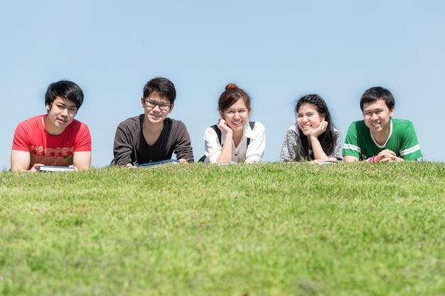 Grupo de amigos que estudam ao ar livre no parque na escola.