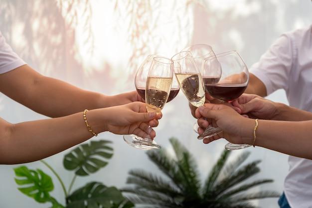 Grupo de amigos que levantam um brinde com os vidros do vinho tinto exteriores no verão.