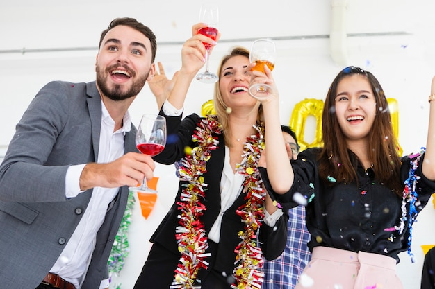 Grupo de amigos que riem comemorando guardar flautas do champanhe ao dançar no partido na sala branca.