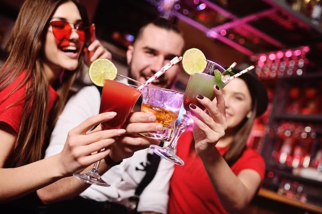 Grupo de amigos-rapaz e duas garotas bonitas se divertindo em uma festa segurando coquetéis