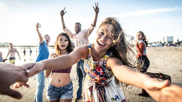 Grupo de amigos se divertindo e dançando na praia. festa de férias na primavera na praia