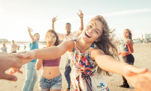 Grupo de amigos se divertindo e dançando na praia