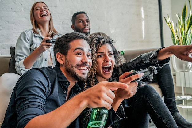 Grupo de amigos se divertindo jogando videogame juntos em casa. conceito de amigos.