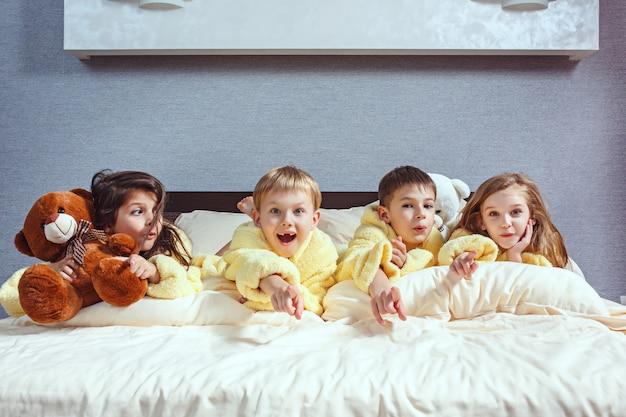 Grupo de amigos se divertindo na cama. crianças rindo felizes, meninos e meninas brincando na cama branca no quarto.