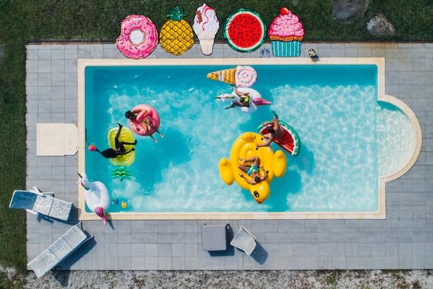 Grupo de amigos se divertindo na piscina com diferentes camas de ar