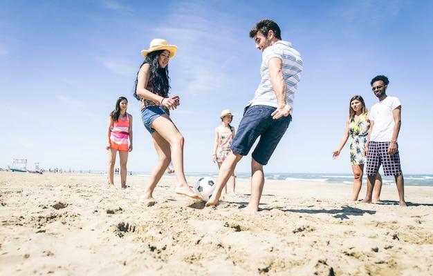 Grupo de amigos se divertindo na praia jogando futebol