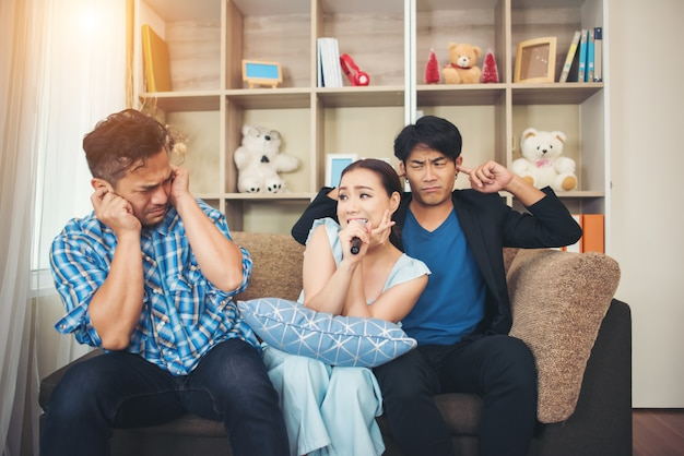Grupo de amigos se divertindo na sala de estar cantando uma música juntos