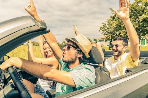 Grupo de amigos se divertindo na viagem de carro pela europa. amigos em férias dirigindo na estrada