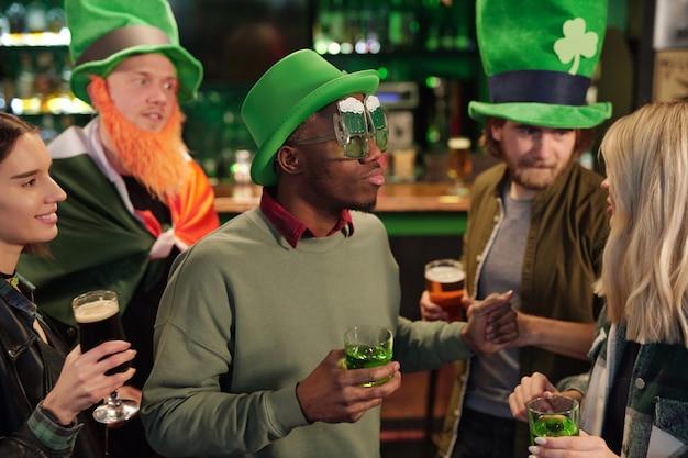 Grupo de amigos se divertindo no bar e bebendo coquetéis durante a celebração do dia de patricks