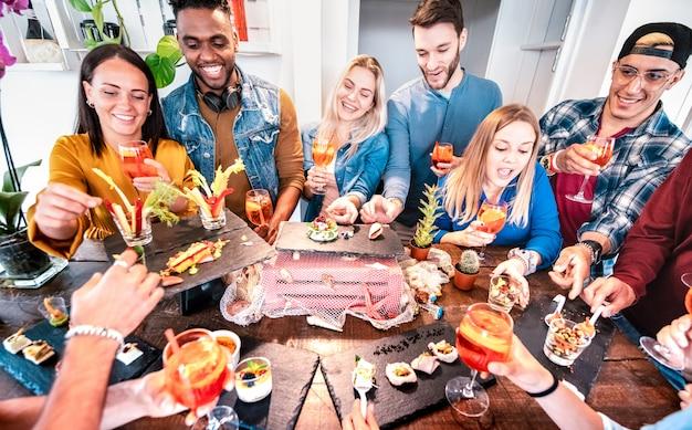 Grupo de amigos se divertindo no buffet pré-jantar bebendo spritz cocktail e comer lanches