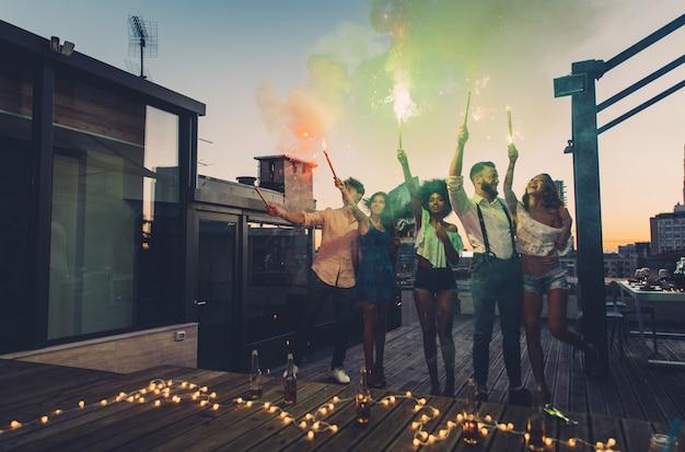 Grupo de amigos se divertindo no telhado de uma bela cobertura