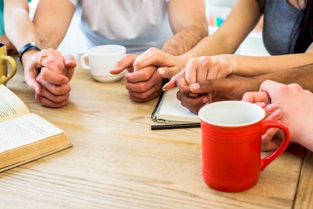 Grupo de amigos, segurando as mãos sobre a mesa com livros e copos de bebida