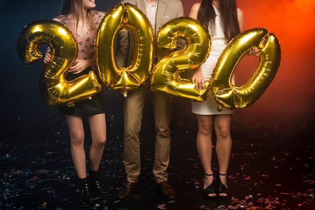 Grupo de amigos segurando balões dourados na festa