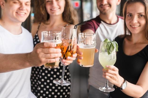 Grupo de amigos segurando diferentes tipos de bebidas alcoólicas