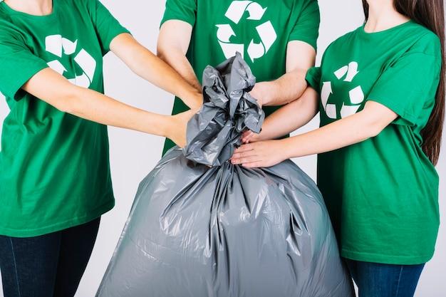 Grupo de amigos segurando o saco de lixo