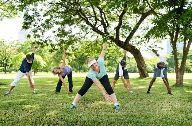 Grupo de amigos sênior, estendendo-se juntos em um parque