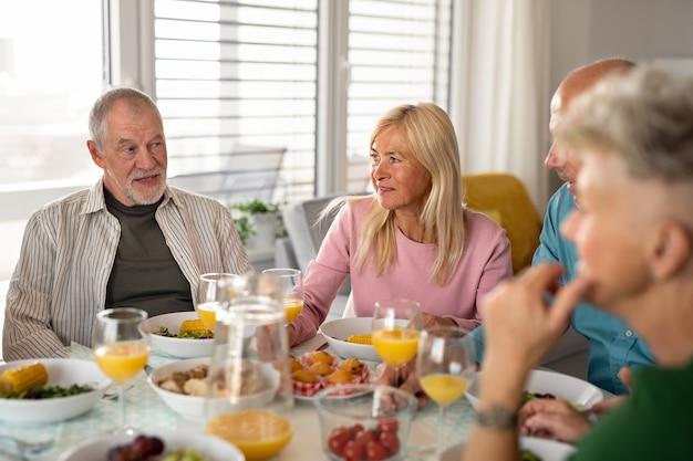Grupo de amigos sênior, festejando dentro de casa, conversando ao comer na mesa.